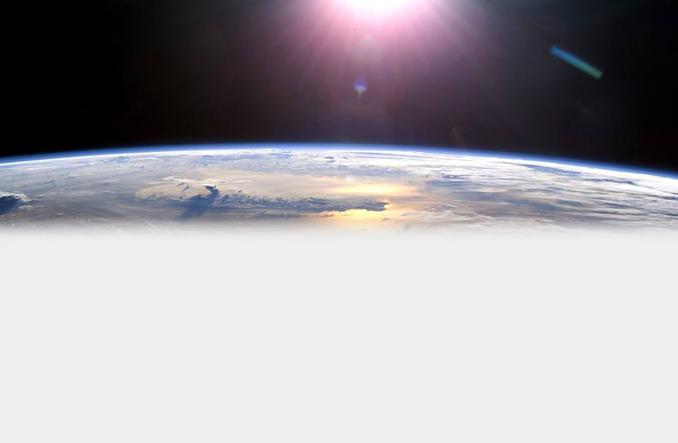 Aerial view of earth from outer space with sun shining down from above.