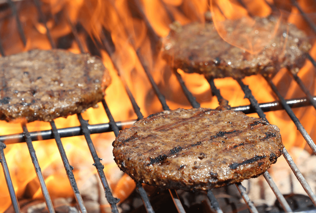 Three plant-based burgers on a grill.
