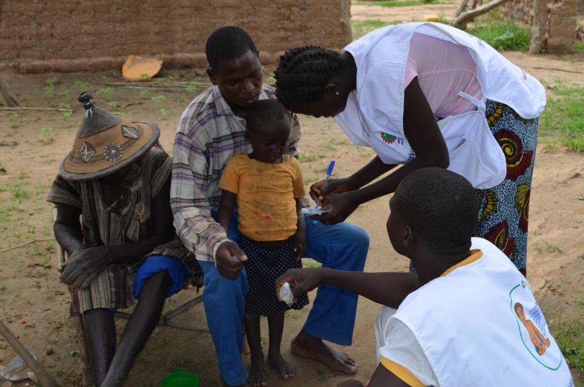 Two African health workers take notes with two African male adults and an African child.